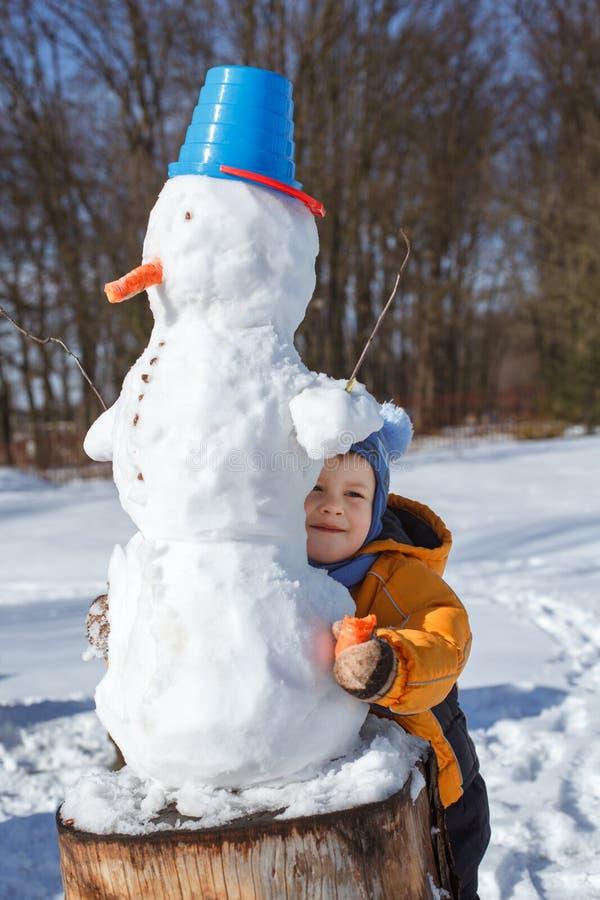 Gullig pys som gör en snögubbe som spelar i snön royaltyfri foto