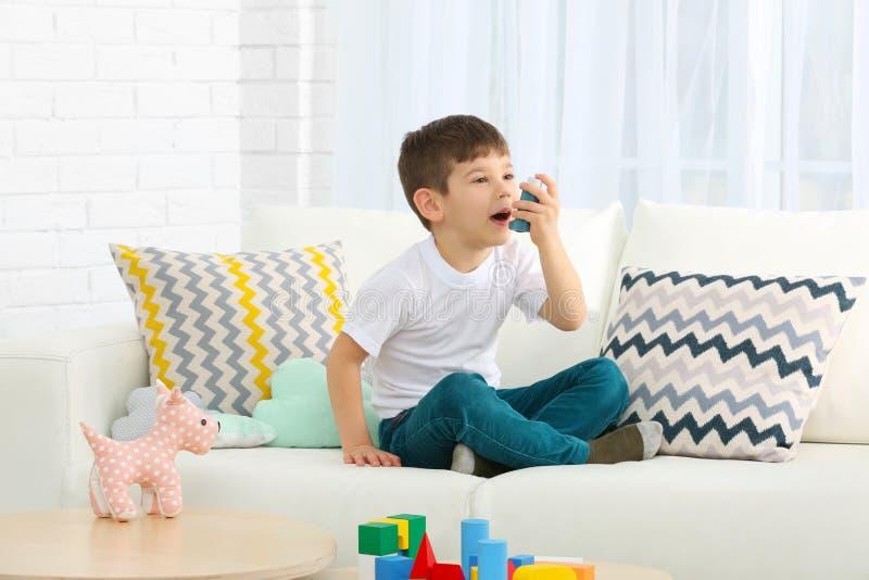 Gullig pys som hemma använder inhalatorn royaltyfri foto