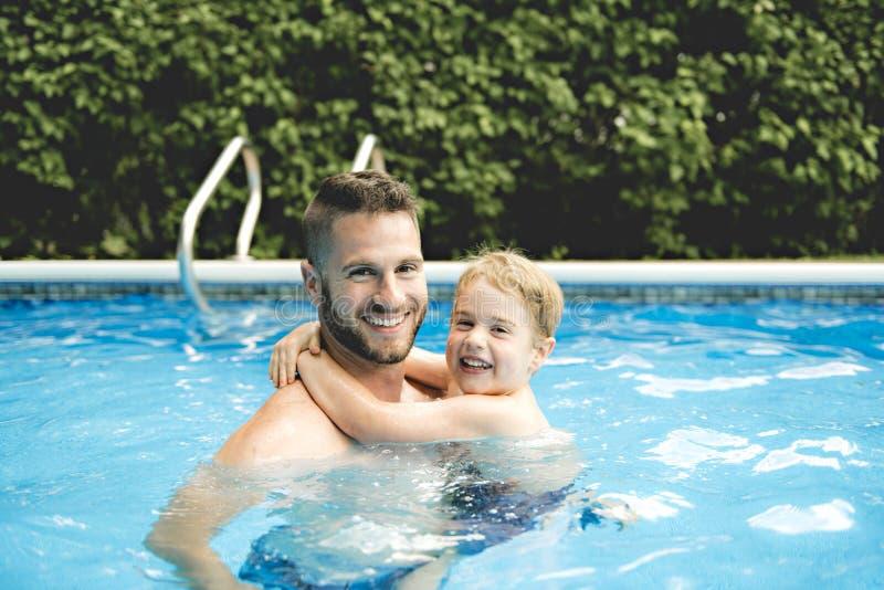 Gullig pys som lär att simma med föräldrar i pöl royaltyfri bild