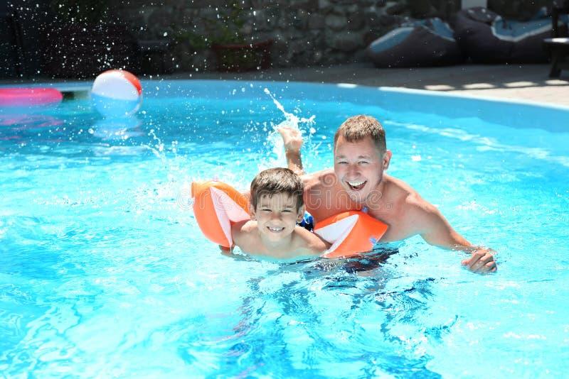 Gullig pys som lär att simma med fadern i pöl royaltyfri foto