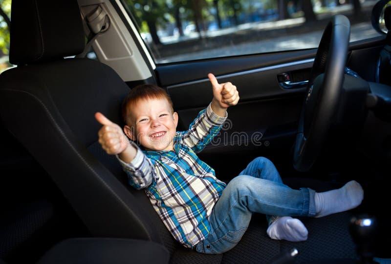 Gullig pys som ler och kör faderbilen royaltyfri fotografi