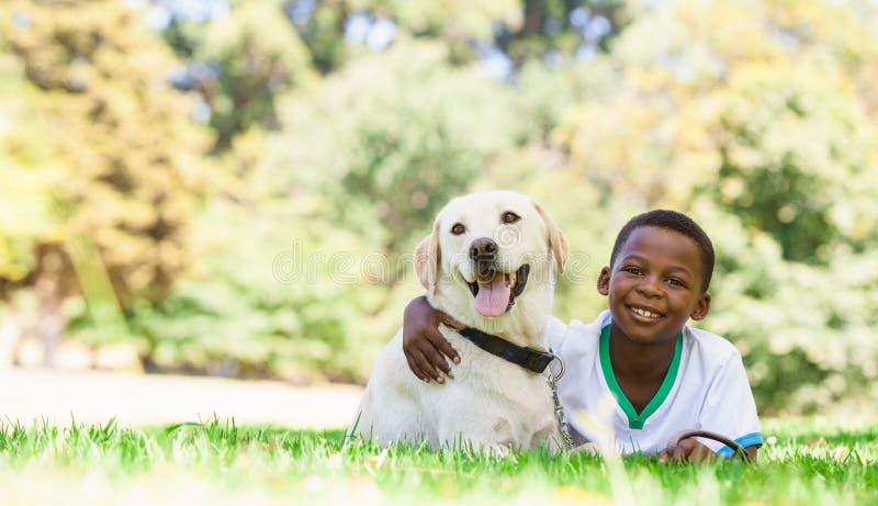 Gullig pys som ligger med den labrador hunden royaltyfri foto