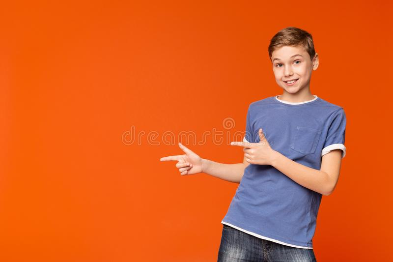 Gullig pys som pekar bort på orange bakgrund arkivfoton