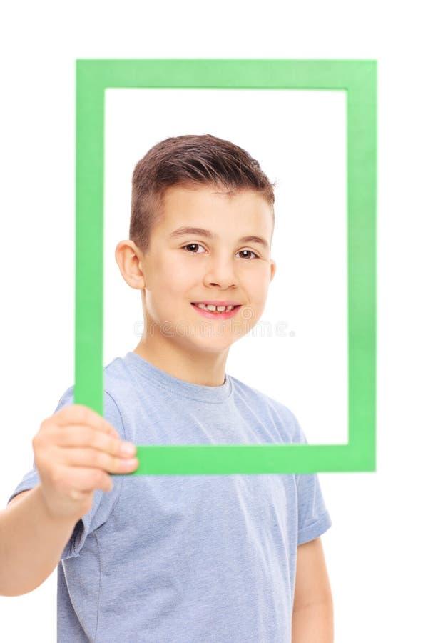 Gullig pys som poserar bak en bildram fotografering för bildbyråer