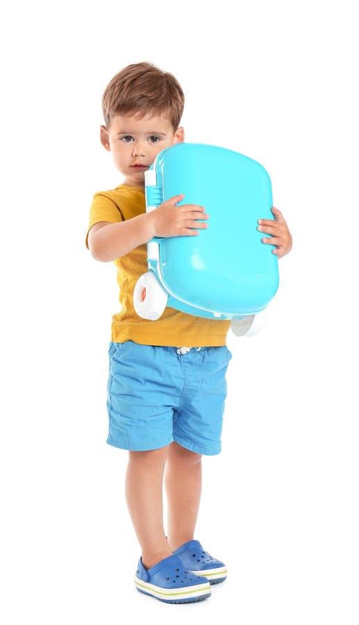 Gullig pys som rymmer den blåa resväskan på vit arkivbilder