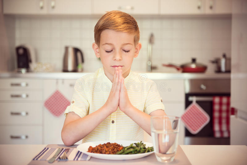Gullig pys som säger bönen, innan att äta mål royaltyfri bild