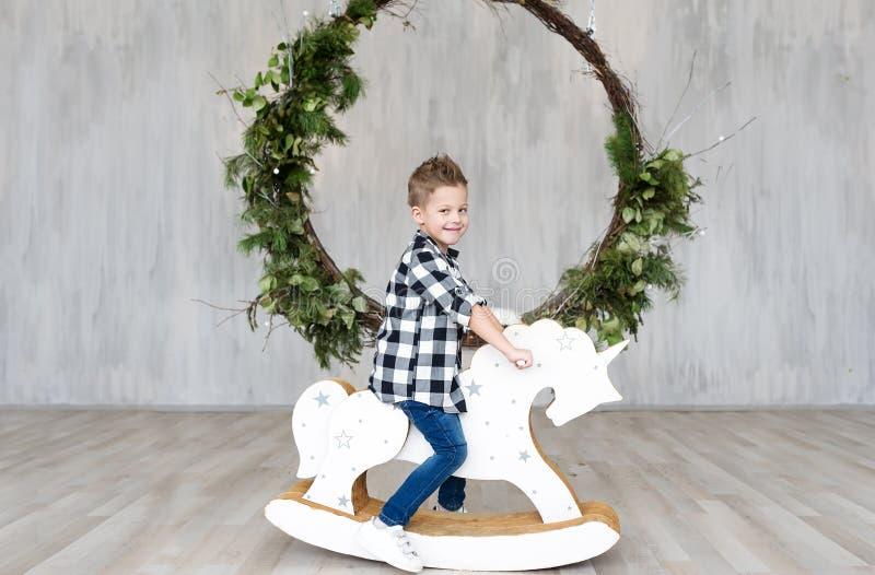 Gullig pys som sitter på en träleksakhäst i en inre av studion arkivfoto