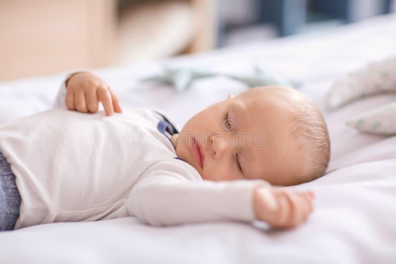 Gullig pys som sover i s?ng royaltyfri fotografi