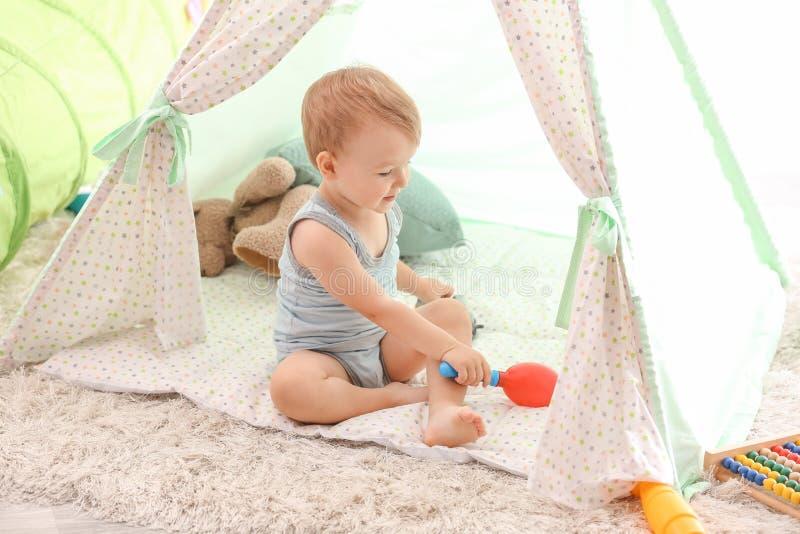 Gullig pys som spelar med leksaker inomhus fotografering för bildbyråer