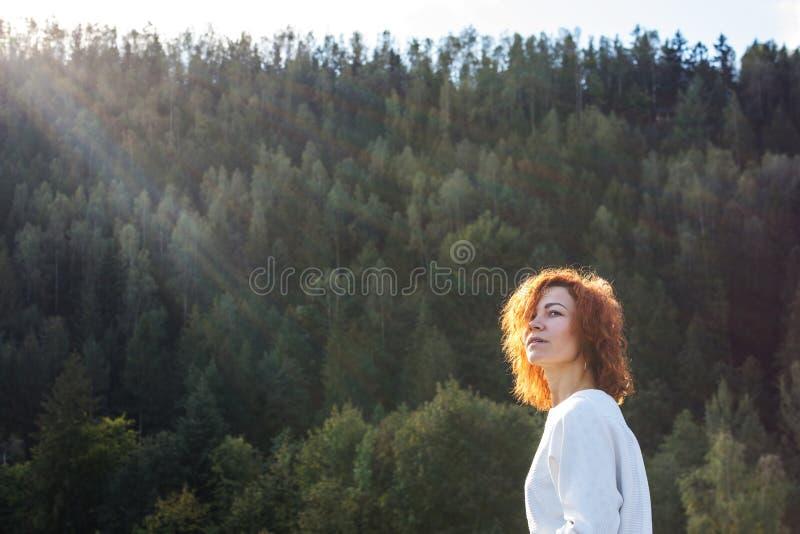 Gullig rödhårig manflicka som tycker om solen i skogen fotografering för bildbyråer
