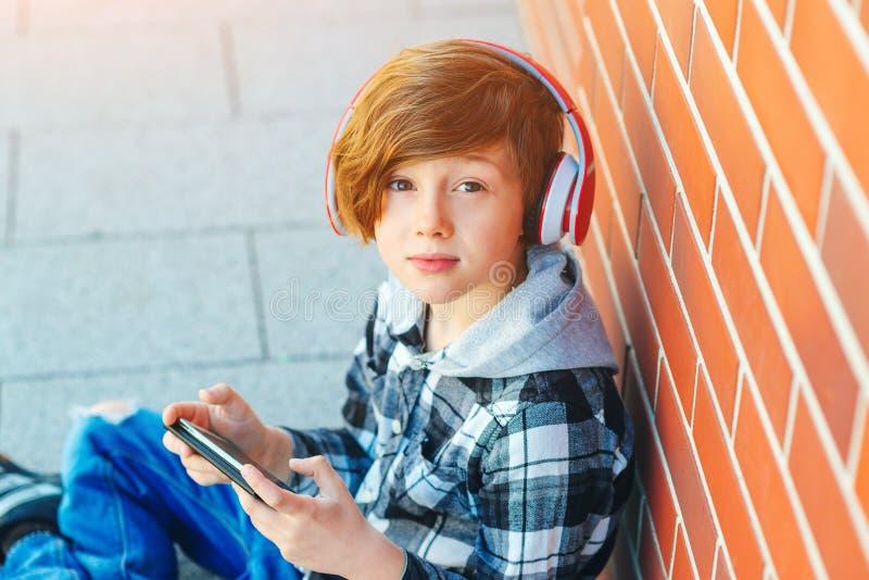 Gullig rödhårig manpojke med den stilfulla frisyren Skolapojke att lyssna till musik i hörlurar Modetonåringen på staden går En s arkivfoton
