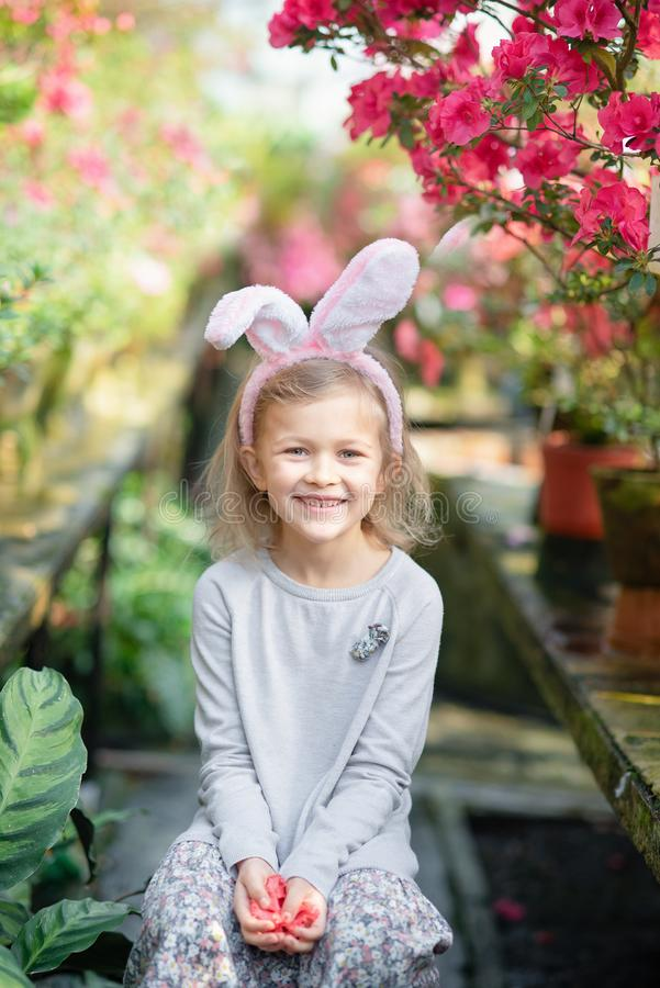 Gullig rolig flicka med öron för påskkanin på trädgården målat gräs för 2 placerade allt för easter för hinkfågelungebegreppet bl fotografering för bildbyråer