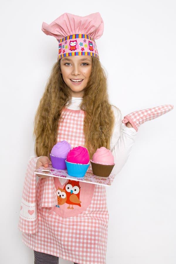 Gullig rolig flicka med slam i köket Flickan lagar mat och bakar hennes muffin, gör en kaka och en slam fotografering för bildbyråer