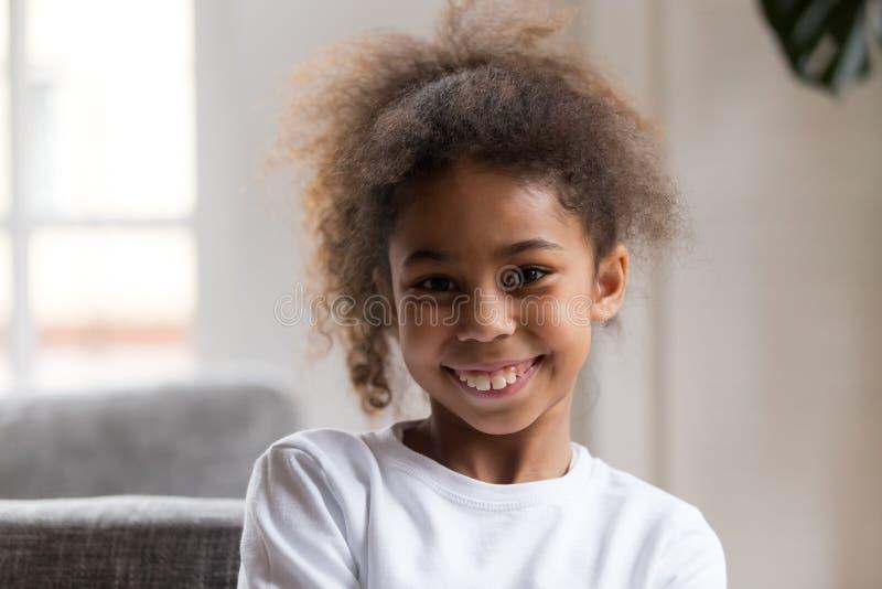 Gullig rolig liten afrikansk amerikanflicka som ser kameran fotografering för bildbyråer