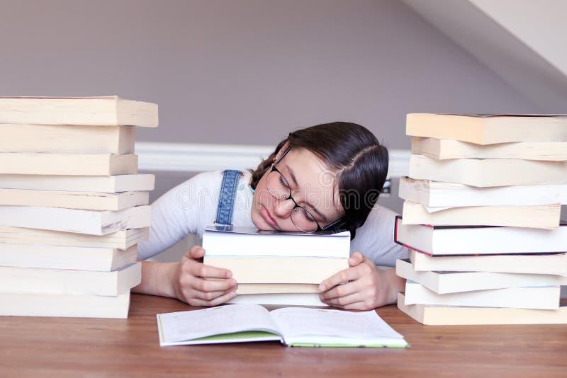 Gullig rolig tweenflicka i exponeringsglas som är trötta av att läsa och att studera att sova på böcker mellan bunten av böcker arkivbilder