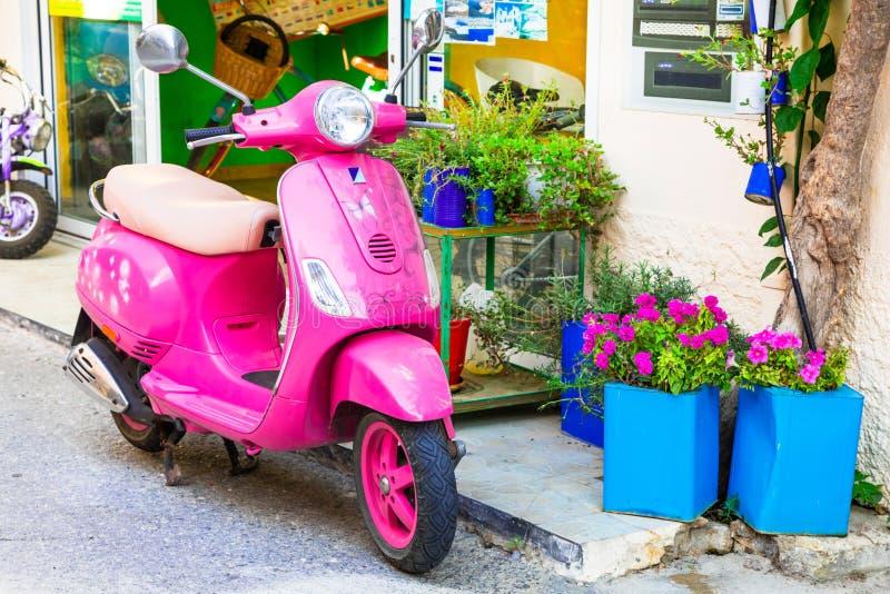 Gullig rosa moped i gator av den Kos ön, Grekland royaltyfria foton