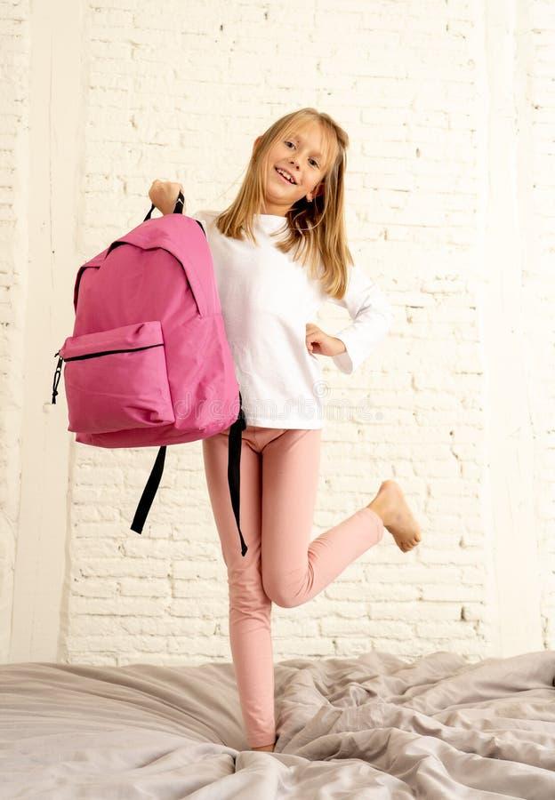 Gullig söt flicka som är upphetsad och som är lycklig i morgonen på hennes första dag till skola som rymmer hennes ryggsäck royaltyfri bild