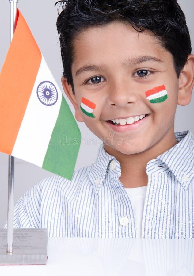Gullig seende indisk unge med den indiska flaggan arkivbilder