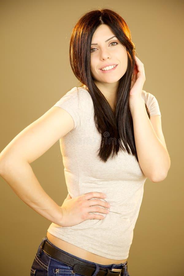 Gullig sexig brunett som poserar i lyckligt le för studio arkivfoton