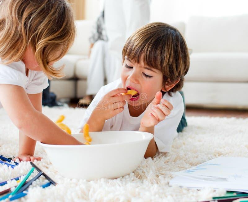 Gullig sibling som äter franska småfiskar på golvet royaltyfria bilder