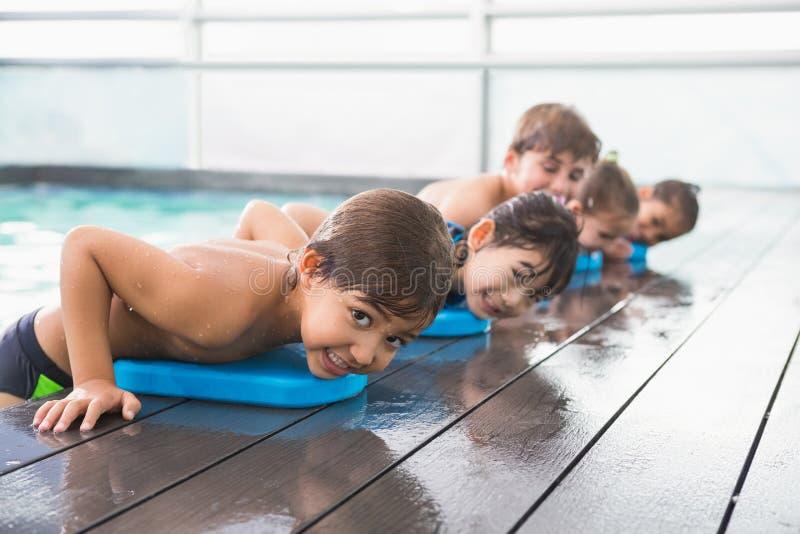 Gullig simninggrupp på pölen arkivbild