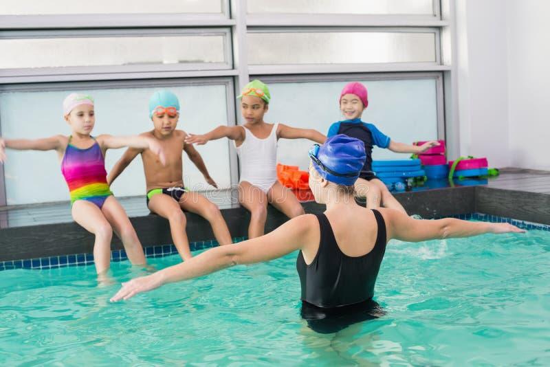 Gullig simninggrupp som håller ögonen på lagledaren arkivfoton