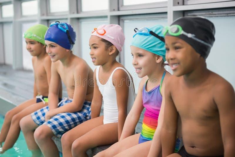 Gullig simninggrupp som ler poolsiden arkivbild