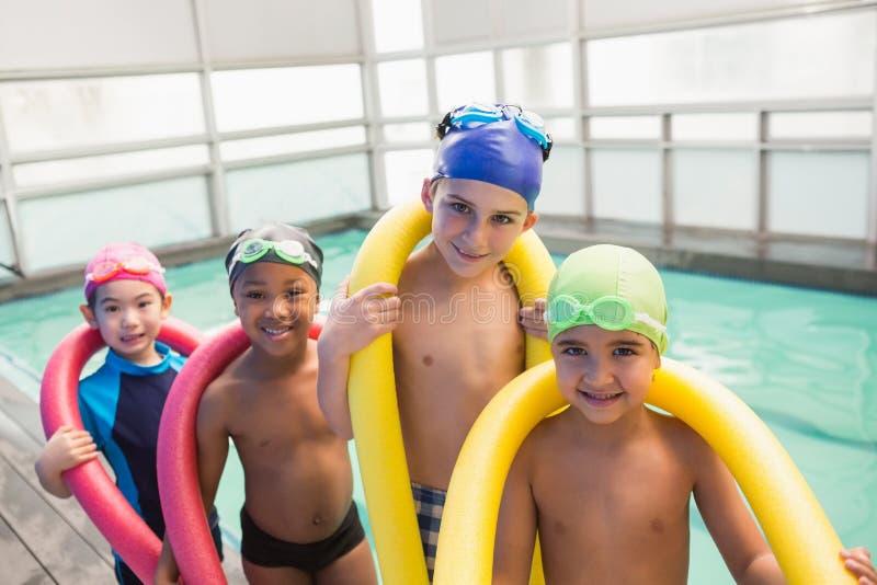 Gullig simninggrupp som ler poolsiden royaltyfri bild