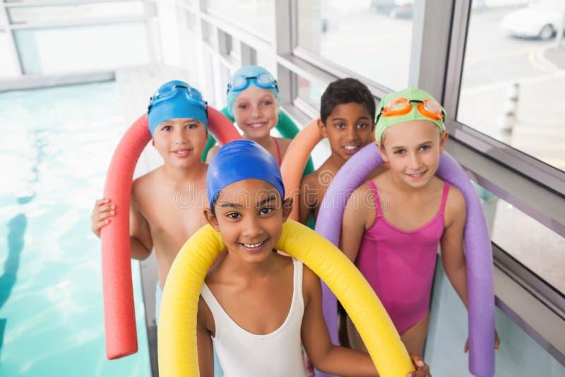 Gullig simninggrupp som ler poolsiden royaltyfri fotografi