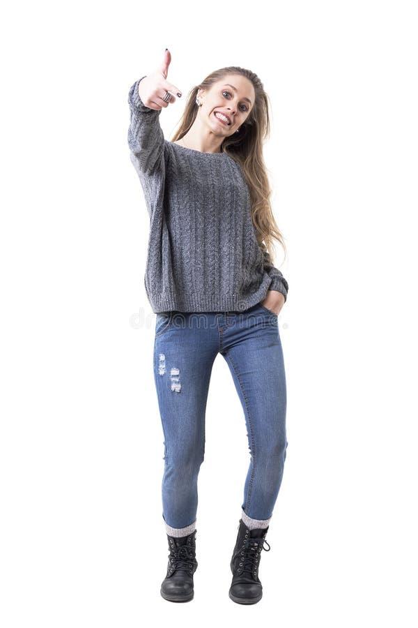 Gullig skämtsam ung charmig kvinna i grått förkläde som pekar fingret som visar dig fotografering för bildbyråer