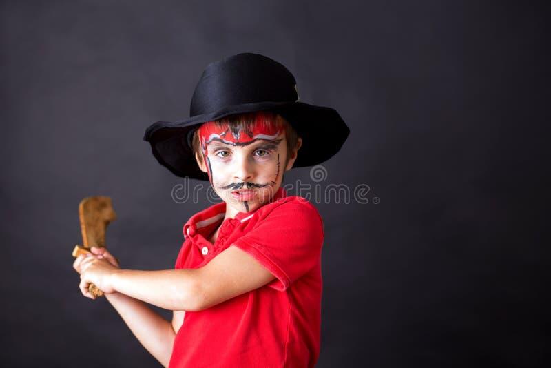 Gullig skolapojke som spelar lekar som målas som, piratkopierar och att rymma svärdet royaltyfria bilder