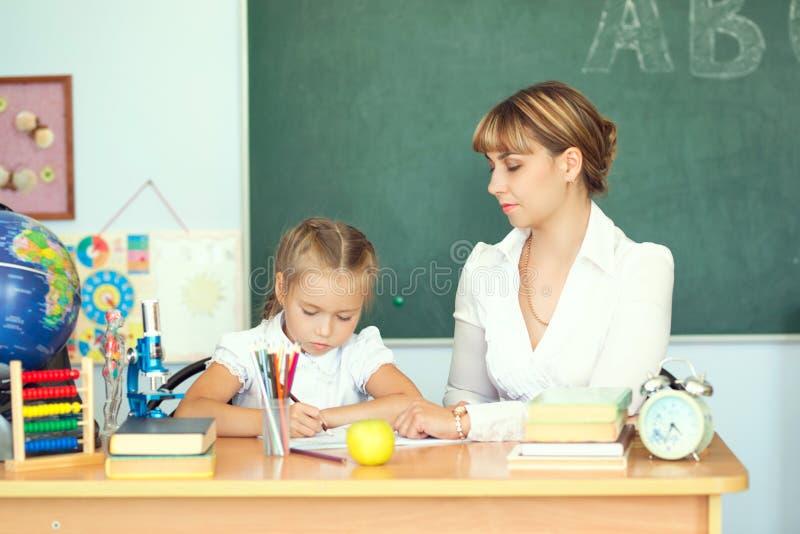 Gullig skolflicka och hennes lärare i ett klassrum royaltyfria foton
