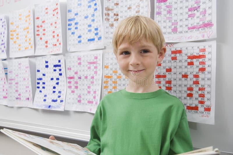 Gullig skolpojke med boken arkivbilder