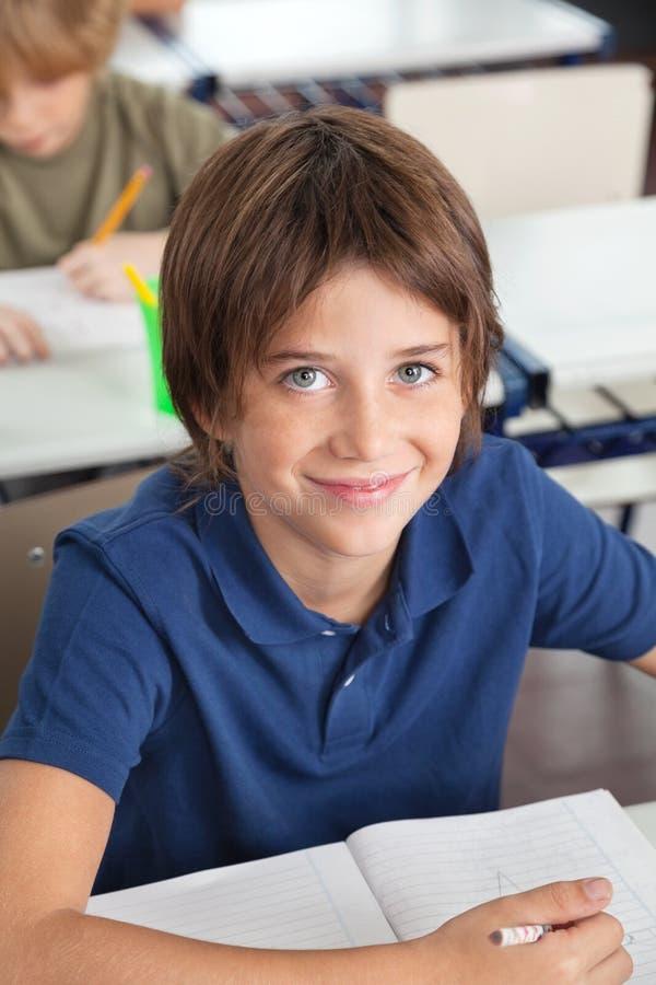 Gullig skolpojke som ler i klassrum arkivbild