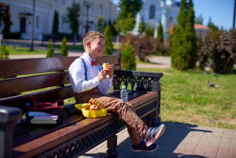 Gullig skolpojke som utomhus äter skolan Sund skolafrukost f?r barn Mat för lunch, lunchboxes med smörgåsar, frukter royaltyfri fotografi