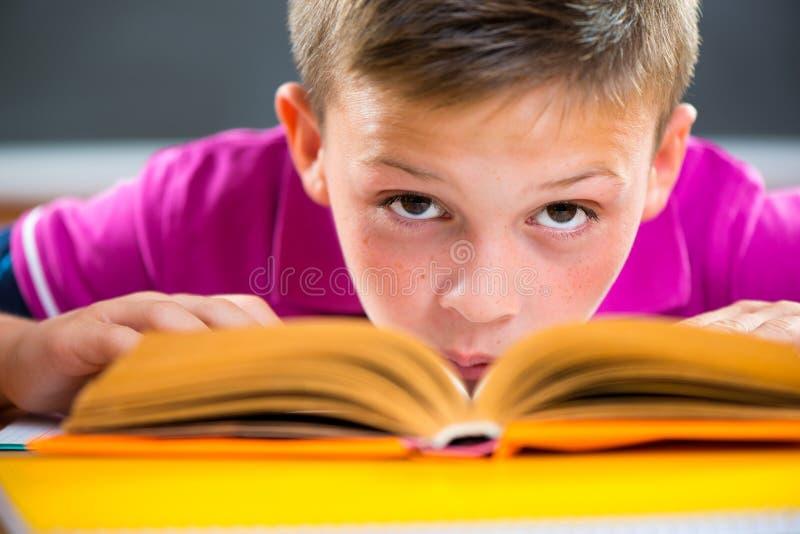 Gullig skolpojkeläsning i klassrum arkivfoto