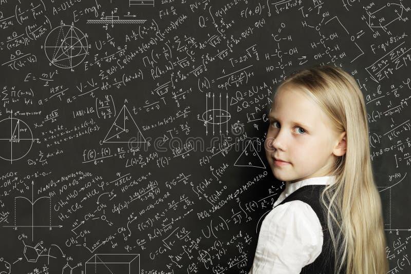 Gullig smart barnstudent på svart tavlabakgrund med vetenskapsformler Lära vetenskapsbegrepp royaltyfria bilder