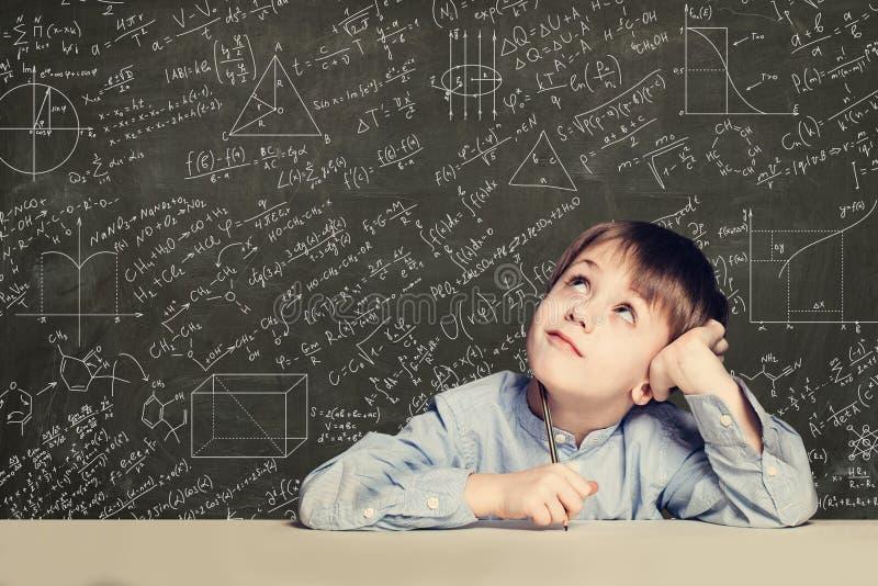 Gullig smart barnstudent på svart tavlabakgrund med vetenskapsformler Lära vetenskapsbegrepp royaltyfria foton