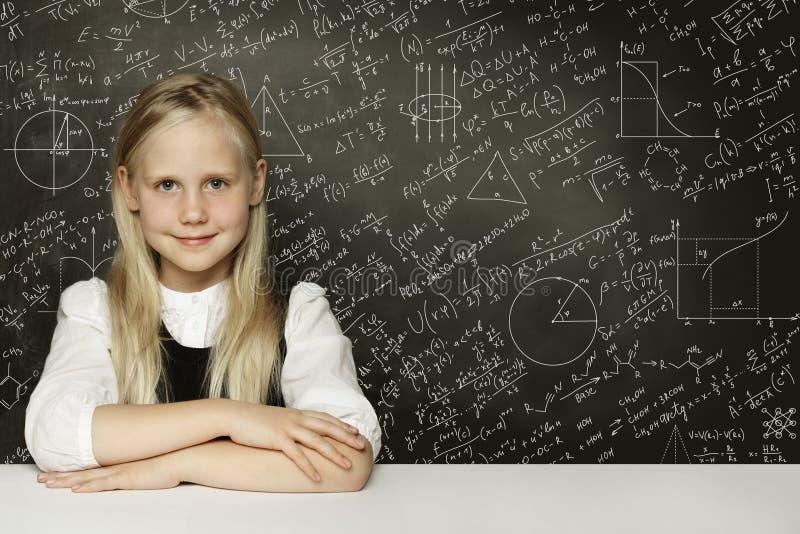 Gullig smart barnstudentflicka på svart tavlabakgrund royaltyfri fotografi