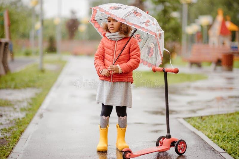 gullig sorgsenhet behandla som ett barn flickan i regnkörningarna till och med pölarna royaltyfria foton