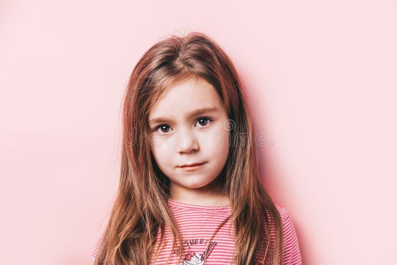Gullig stående av lilla flickan med långt hår på rosa bakgrund royaltyfria bilder