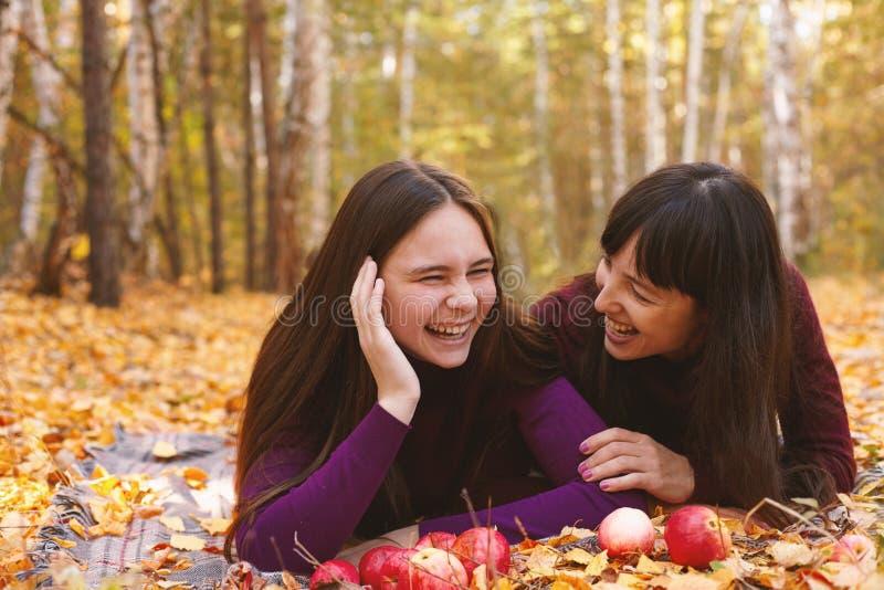 Gullig stående av modern och dottern i höstskogen arkivfoto