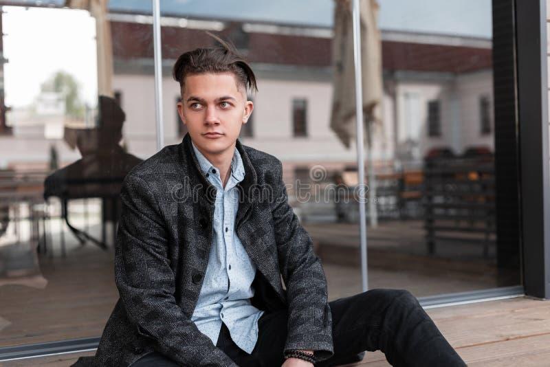Gullig stilig ung man i ett rutigt grått omslag i en klassisk skjorta i svart jeans med en stilfull frisyr som ner sitter royaltyfri fotografi
