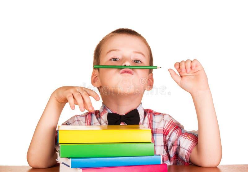 Gullig student med böcker och blyertspennan bak hans skrivbord arkivfoto