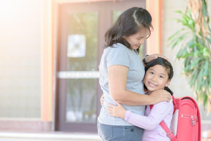 Gullig student med bagschool som kramar hennes moder arkivfoto
