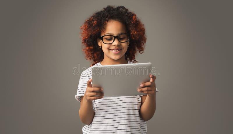Gullig svart barnflicka som använder bakgrund för minnestavlaobstudio royaltyfria foton