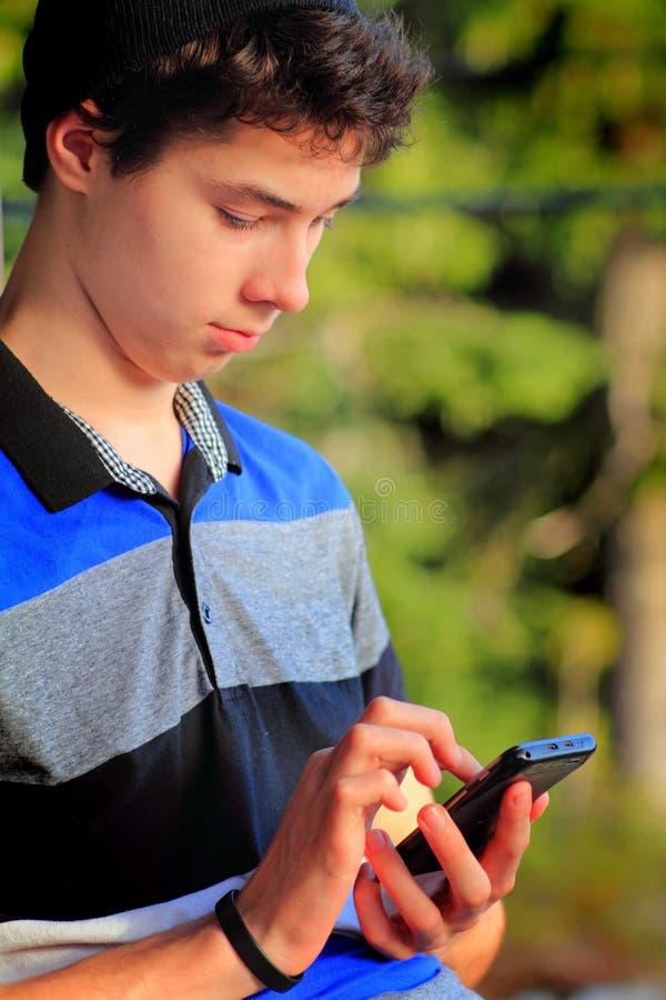 gullig teen texting för pojke arkivbild