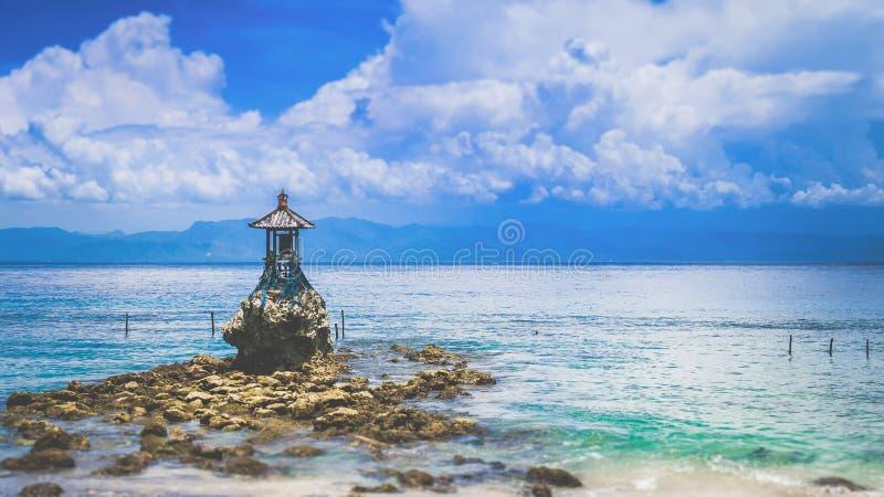 Gullig tempel på kusten vid havet på Nusa Penida med dramatiska moln ovanför Bali, Indonesien royaltyfria bilder
