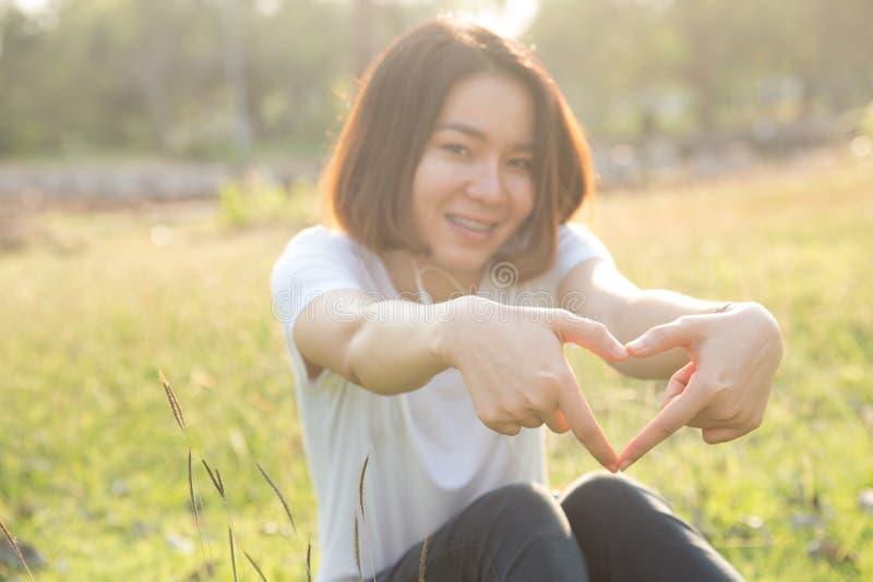 Gullig thailändsk asiatisk form för flickaförälskelsehjärta med henne händer royaltyfri fotografi
