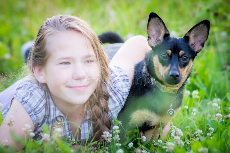 Gullig tonårig flicka med hunden för svart hund royaltyfri fotografi